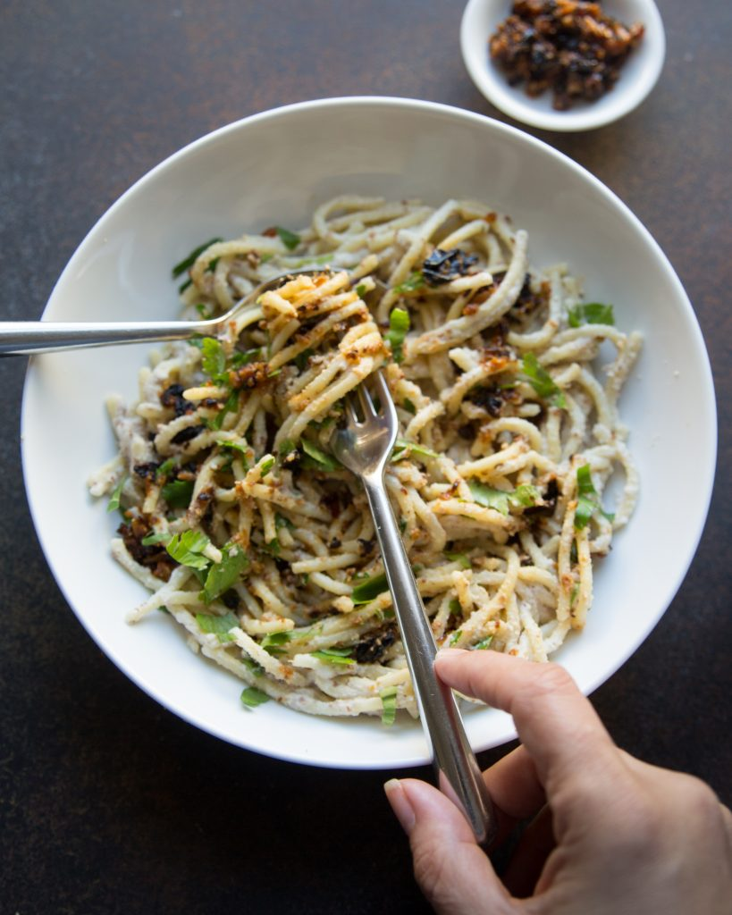 Hands twirling spaghetti in almond cream sauce with pockets of fiery cauliflower make this a keepsake addition to your vegan cauliflower recipes.
